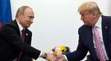 President Donald Trump shakes hands with Russian President