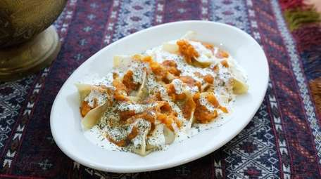 Mantu dumplings are double-drizzled with sauces of tomato
