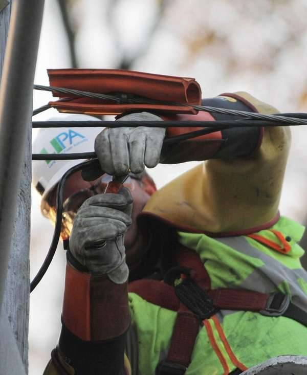 A LIPA worker repairs an electric line in