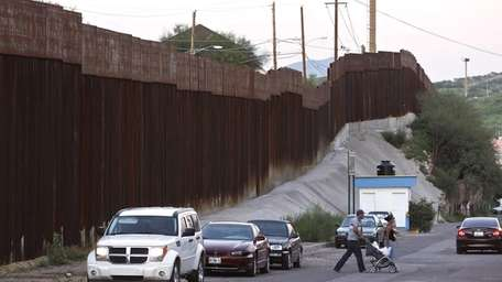 Vehicles are parked along the border fence as