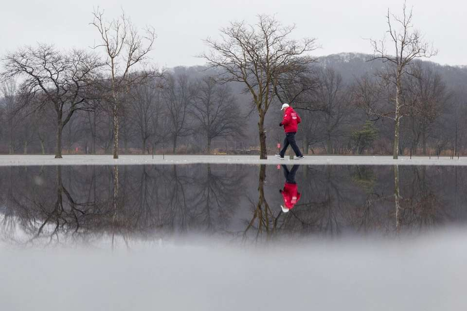 Reflected in a puddle, a man walks through