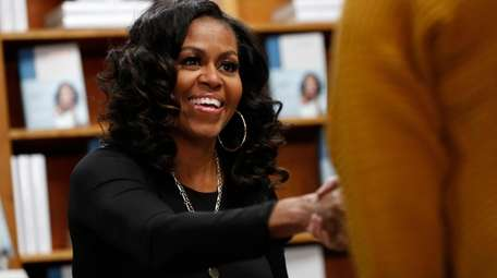 Former first lady Michelle Obama greets people as