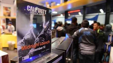 Gamers wait in a Game Stop store to