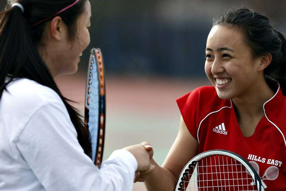 Syosset first singles player Vivian Cheng, left, shakes