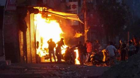 A store is engulfed in flames amid mob