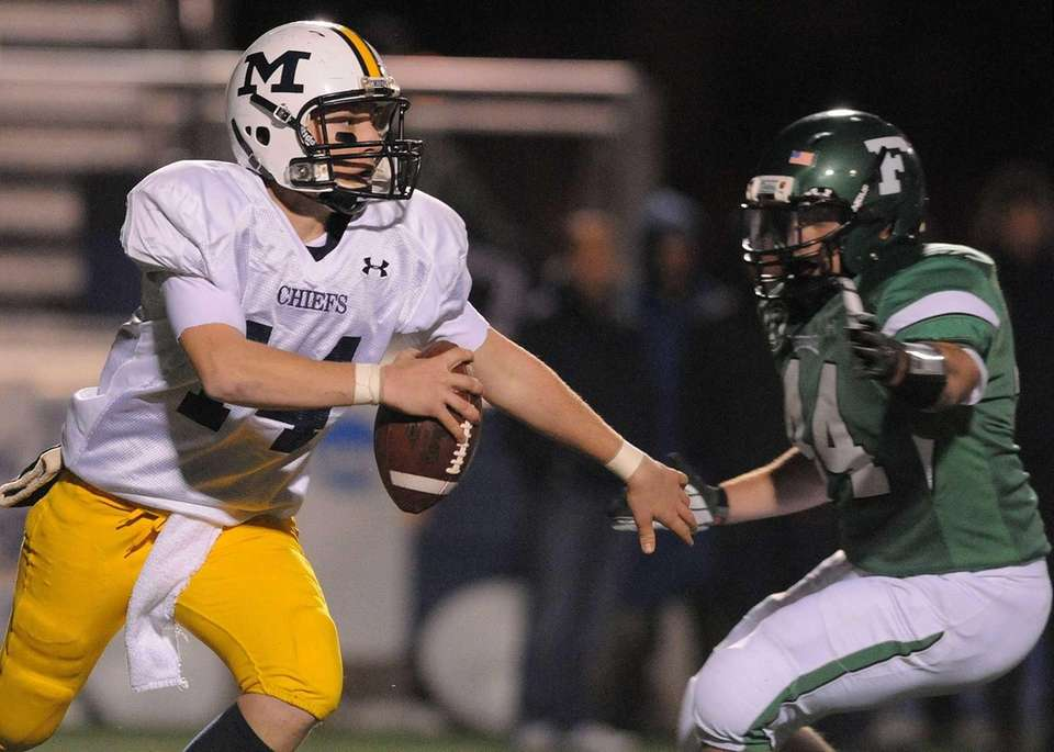 Massapequa quarterback Paul Bentz, left, tries to evade