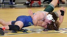 Hauppauge's Danny Mauriello (blue) wrestles Longwood's Zach Soriano