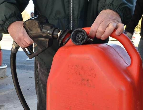 A man fills up his gas can while