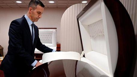 Brueggemann Funeral Home funeral director Craig DeMaio adjusts
