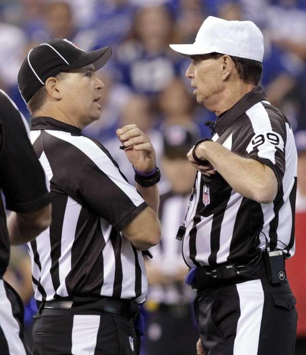 Referee Tony Corrente, right, confers with an associate