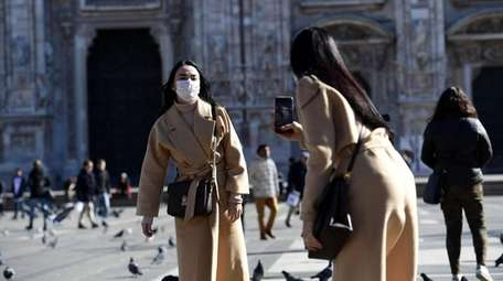 Women wearing protective masks take pictures in Piazza