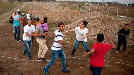 Israelis run for cover during a Hamas rocket