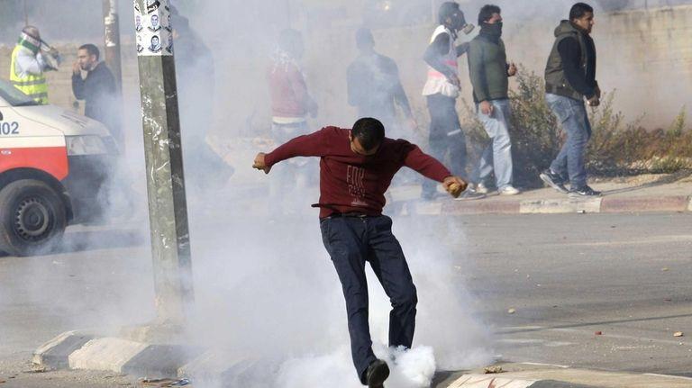 A Palestinian demonstrator kicks away a tear-gas canister