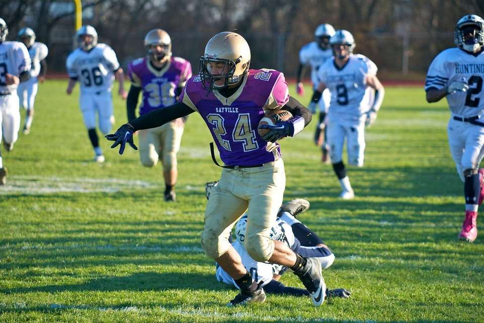 Sayville running back Chris Belcher is stopped just