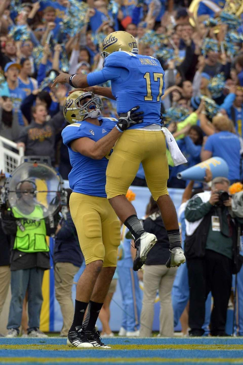 UCLA quarterback Brett Hundley, right, jumps into the