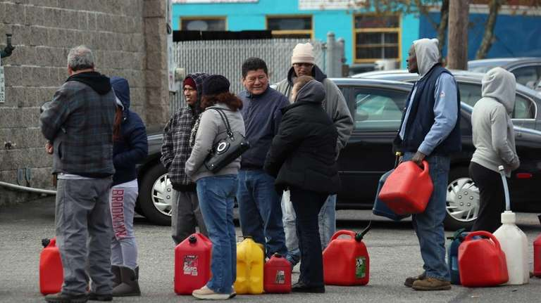 Customers stand in line for gas at a