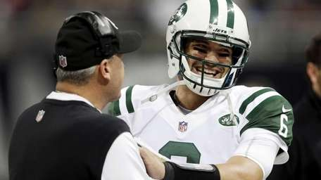 Jets quarterback Mark Sanchez, right, smiles as he