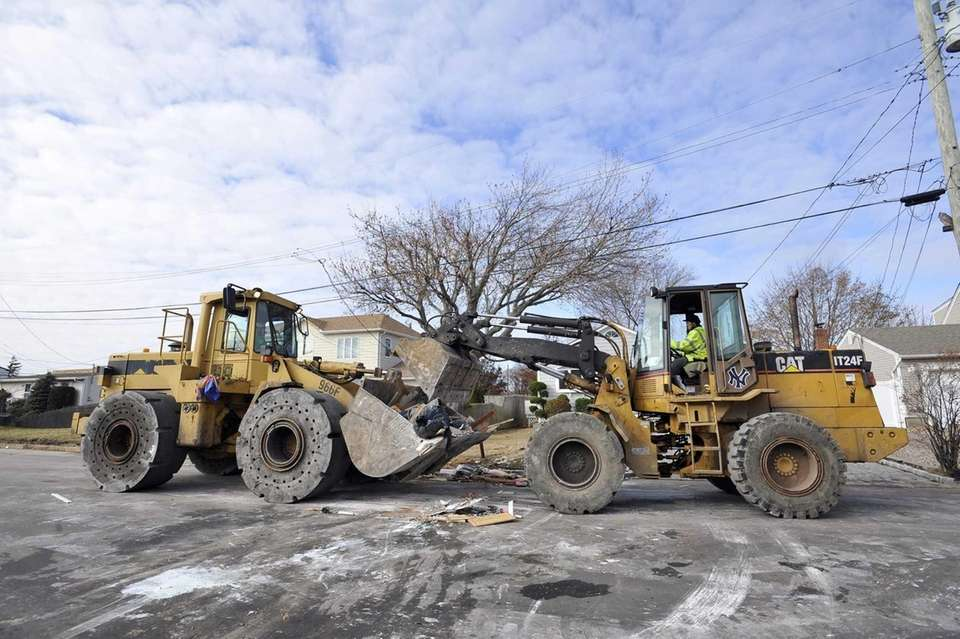 Payloaders work in tandem to remove debris on