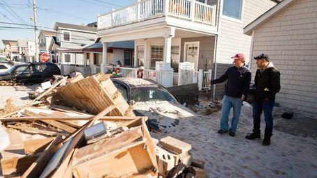 Neighbors Joe Valentino, left and Chaim Lazarus survey