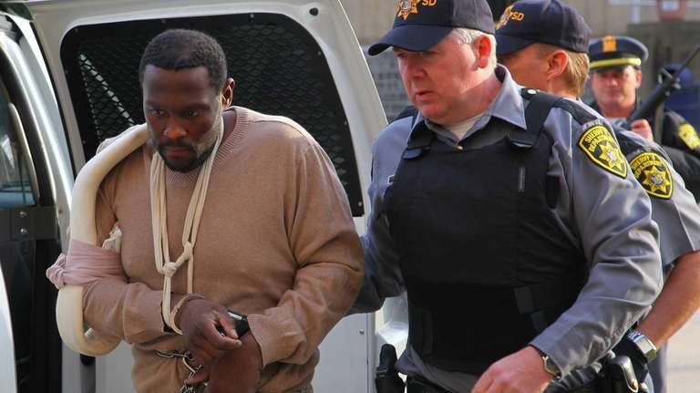 Darrell Fuller is escorted into Nassau County court