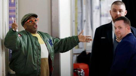Director Spike Lee, left, gestures in a hallway