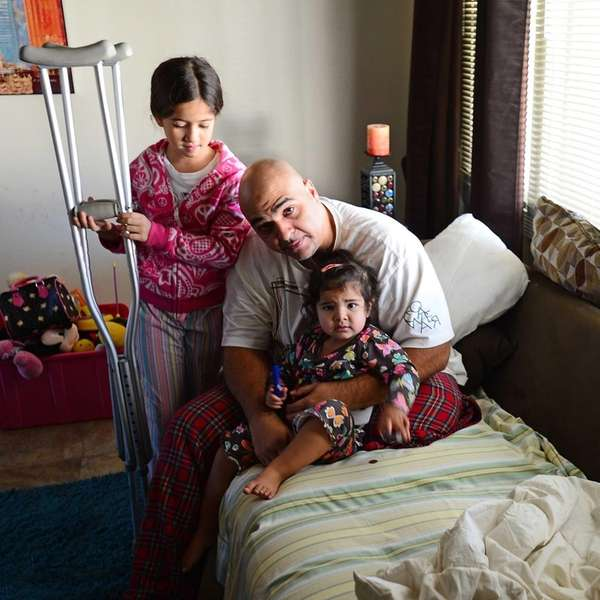 Kenneth Martinez sits on the couch with daughters,