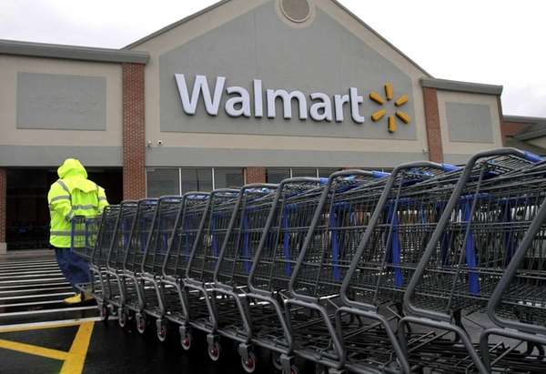 A worker pulls a line of shopping carts