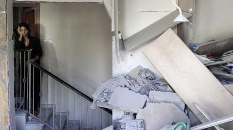 An Israeli woman reacts at her house hit
