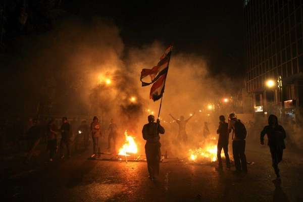 An Egyptian protester carries a tattered national flag