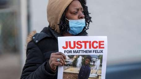 "A supporter holds a ""Justice for Matthew Felix"""
