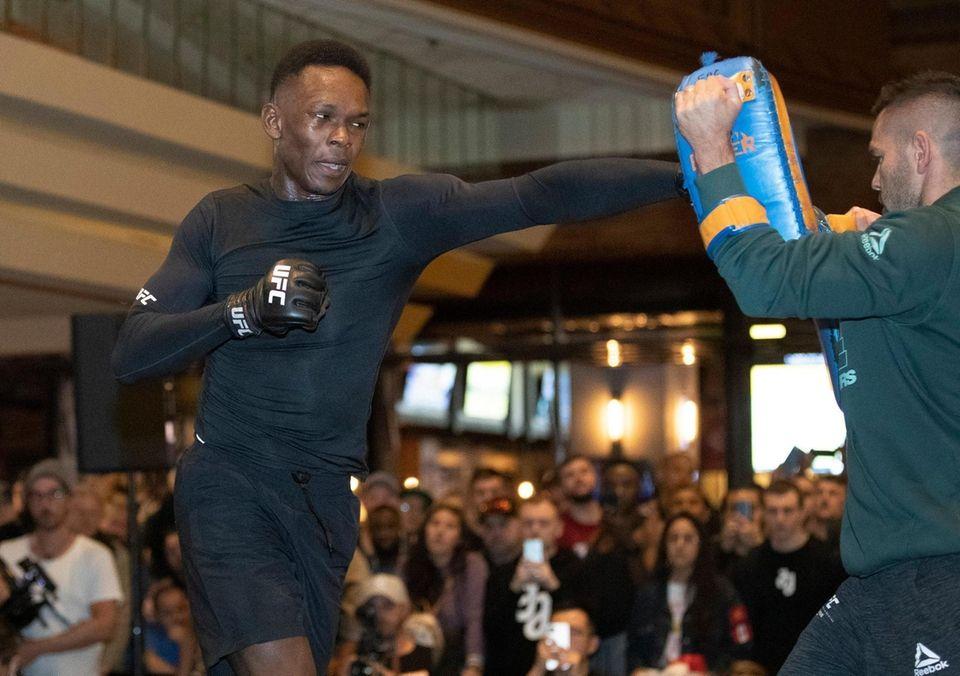 UFC middleweight champion Israel Adesanya, left, works on