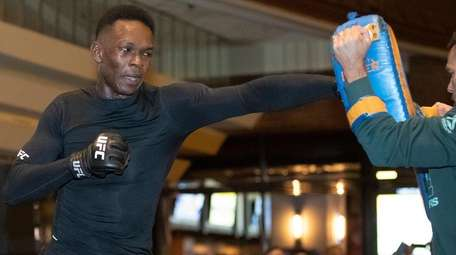 UFC middleweight champion Israel Adesanya, left, works on