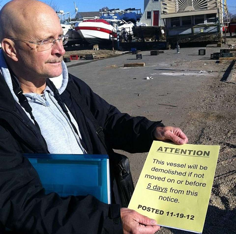 Seaford resident Peter Kopher holds sign he found