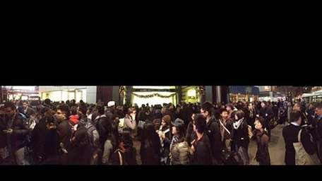Passengers gather outside of Penn Station as the