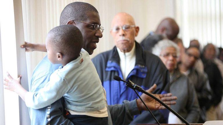 Jose Johnson, of Westbury, holds his son Andrew,
