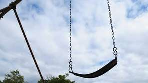 An empty swing hangs on a swingset at