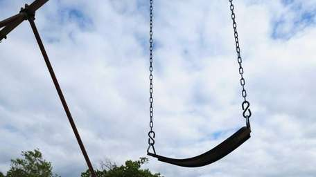 An empty swing hangs on a swingset at