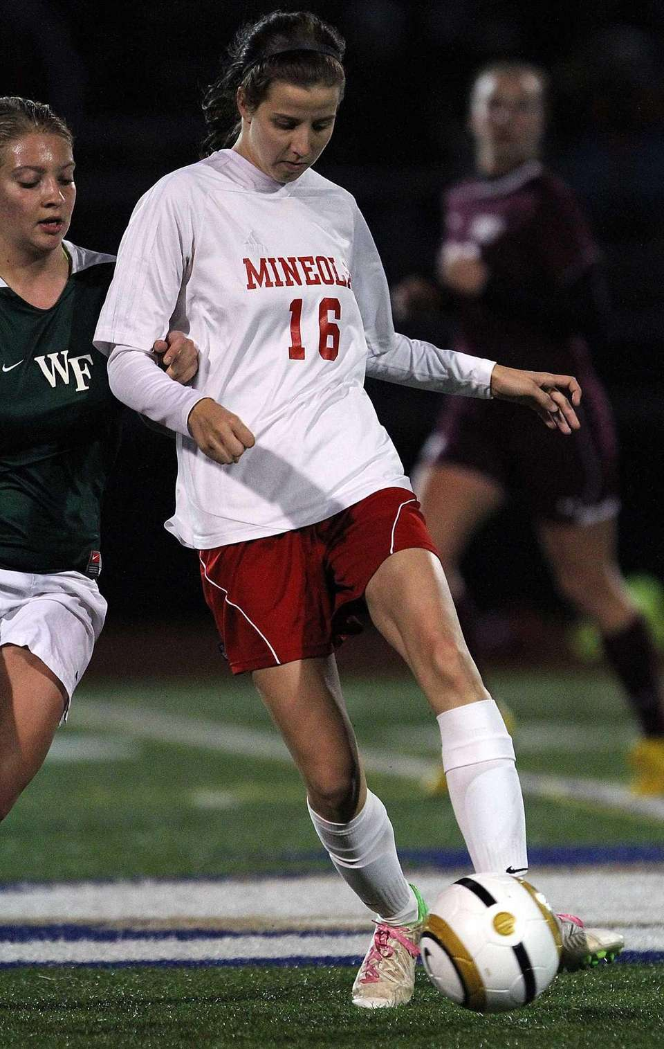 Mineola's Nina Ribero fights for the ball during