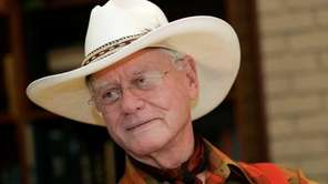 Larry Hagman listens to a reporter's question while