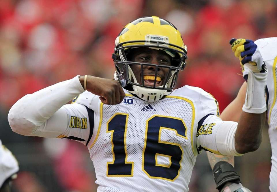 Michigan quarterback Denard Robinson celebrates his 67-yard touchdown