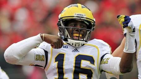 Michigan quarterback Denard Robinson celebrates his 67-yard touchdown
