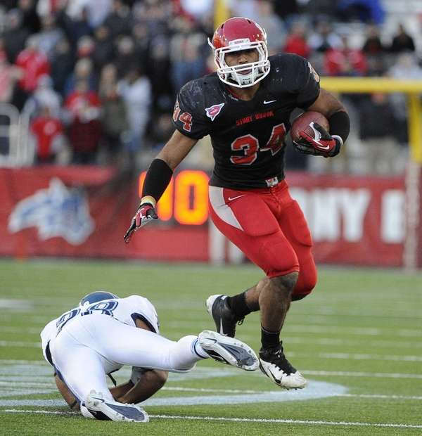 Stony Brook's Marcus Coker evades a tackle by
