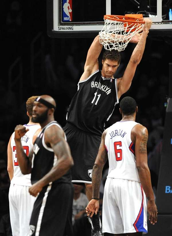 Brook Lopez hangs on the rim after dunking