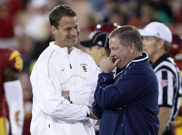 Southern California coach Lane Kiffin, left, talks with