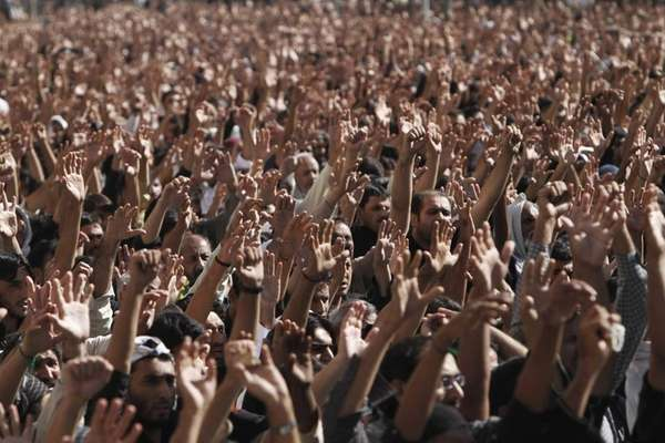 Pakistani Shia Muslims raise their hands as they