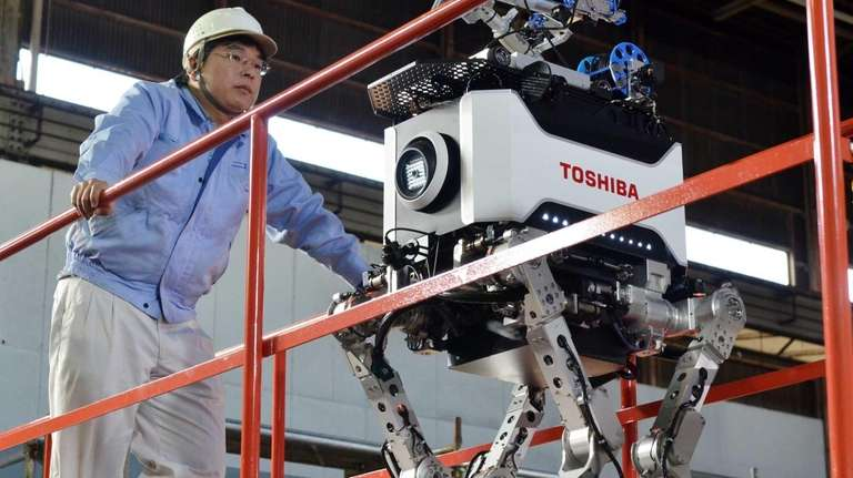 Engineers inspect Toshiba's four-legged robot during a demonstration