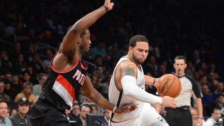 Brooklyn Nets' Deron Williams, right, drives past Portland