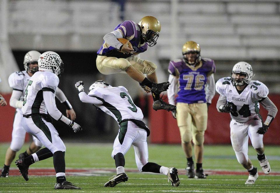 Sayville quarterback Zachary Sirico leaps over Westhampton's Zach