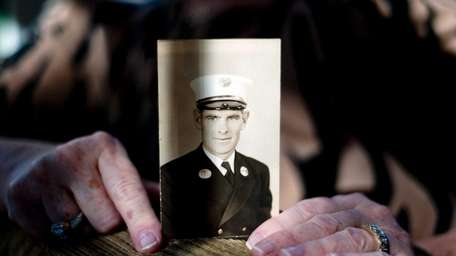 Kathleen Stanco holds a photograph of her father,