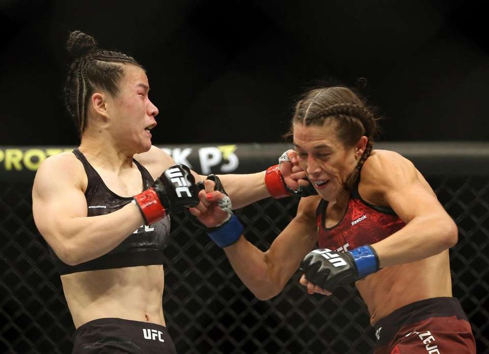 Zhang Weili, left, connects with a punch to
